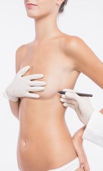 Cirujano plástico dibujando líneas en el cuerpo de la mujer