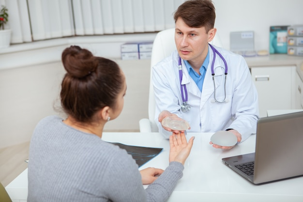Cirujano plástico profesional mostrando implantes mamarios de silicona a su paciente.