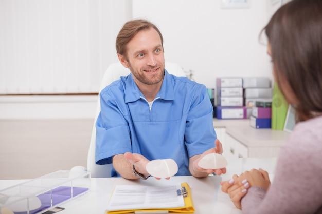 Cirujano plástico que muestra implantes mamarios a una paciente