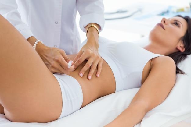 Cirujano que hace la inyección en el cuerpo femenino. concepto de liposucción