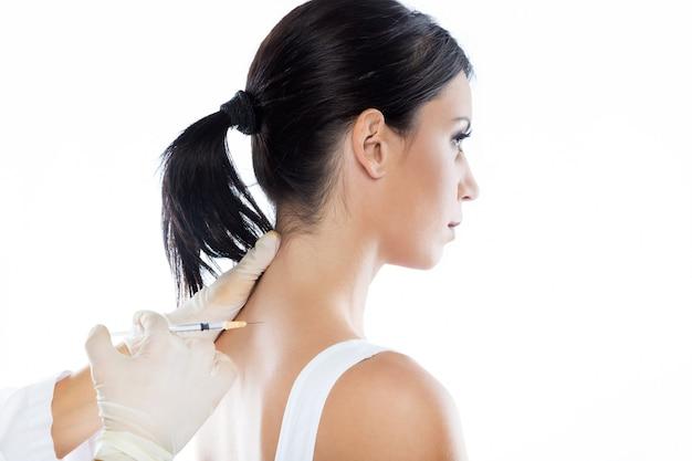 Cirujano que hace la inyección en el cuerpo femenino. concepto de terapia neuronal.