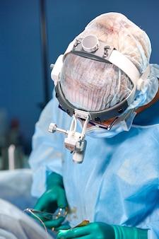 Cirujano realizando cirugía de aumento de senos en el quirófano del hospital. cirujano en máscara con lupas durante el procedimiento médico.