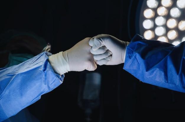 Cirujano unir manos juntas en la sala de operaciones en el hospital