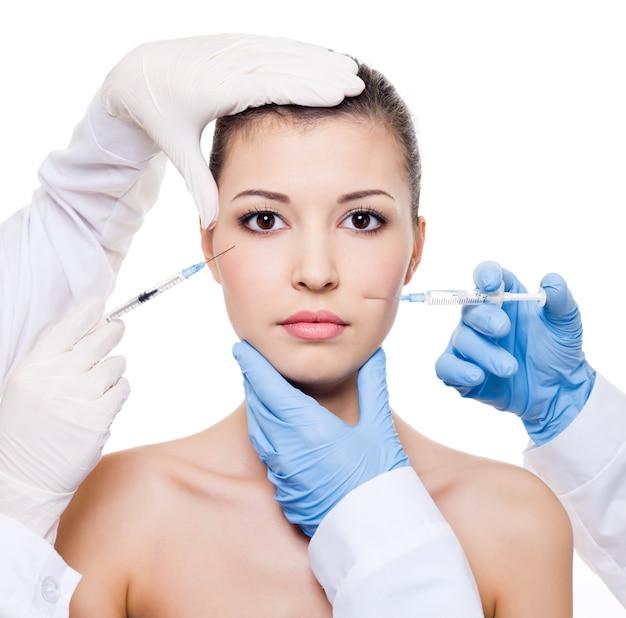 Cirujanos plásticos que dan la inyección de botox en la piel femenina de los ojos y los labios blanco aislado