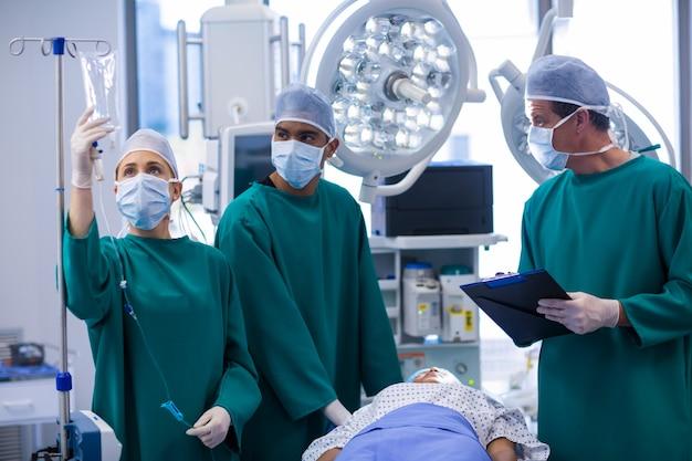 Cirujanos que ajustan goteo intravenoso en quirófano