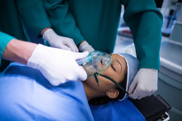 Cirujanos que ajustan la máscara de oxígeno en la boca del paciente en quirófano