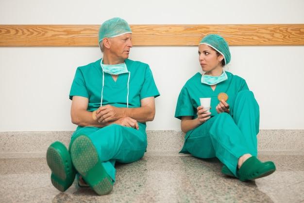 Cirujanos que tienen un descanso en el pasillo