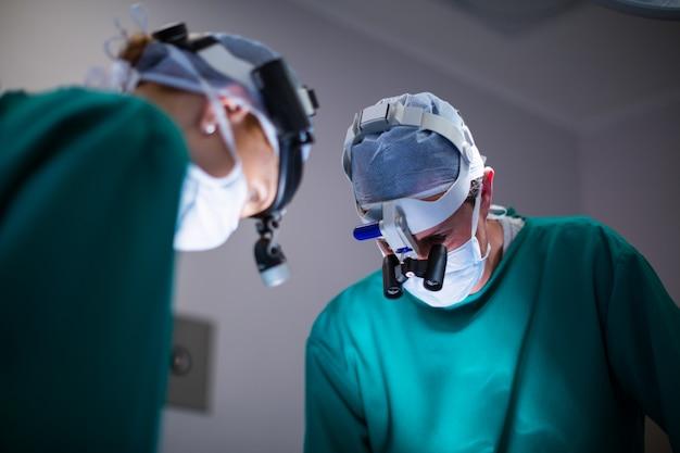 Cirujanos que usan lupas quirúrgicas mientras realizan la operación