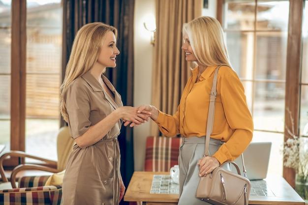 Cita. dos mujeres reunidas en el café y mirando alegre