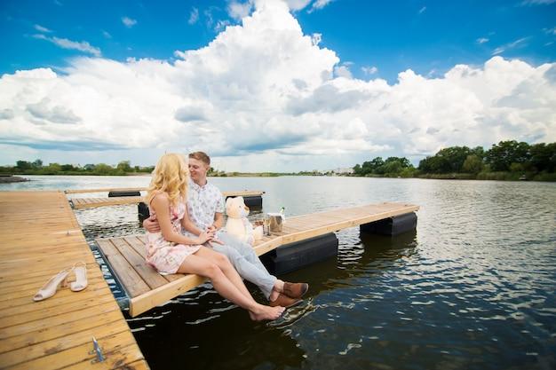 Cita romántica sorpresa. un chico joven y una chica en un muelle de madera. abraza y besa mientras estás sentado en el muelle. historia de amor romantica