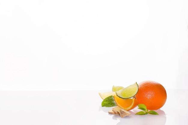 Cítricos frescos de naranja, limón, lima y menta sobre un fondo blanco