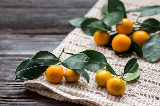 Citrus calamondin con hojas sobre una servilleta de lino sobre tabla de madera.