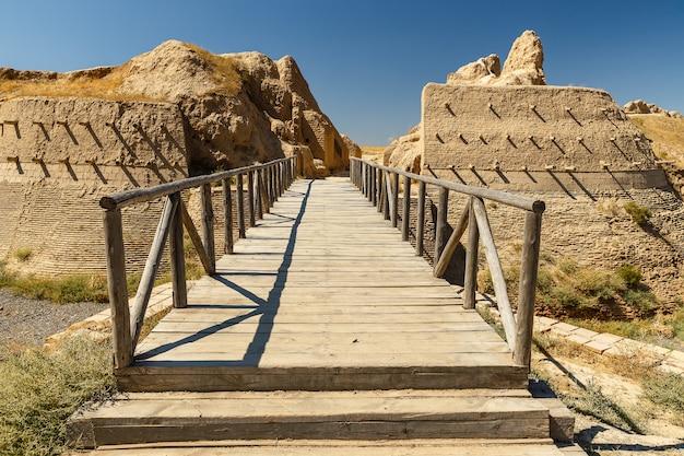 Ciudad arqueológica sawran, kazajstán, puente de madera en frente de la entrada principal