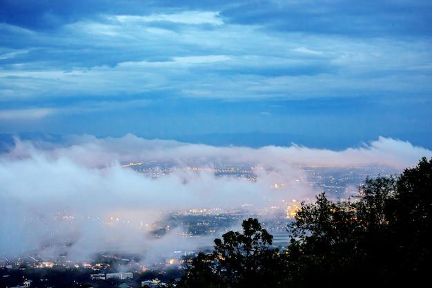 La ciudad de chiang mai en el paisaje de la montaña doi suthep en el cielo crepuscular con nubes brumosas