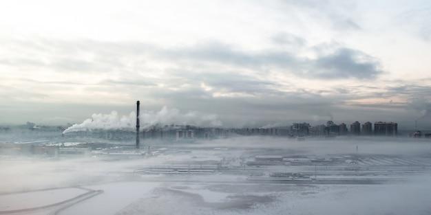 Ciudad gris de la mañana en niebla y humo.