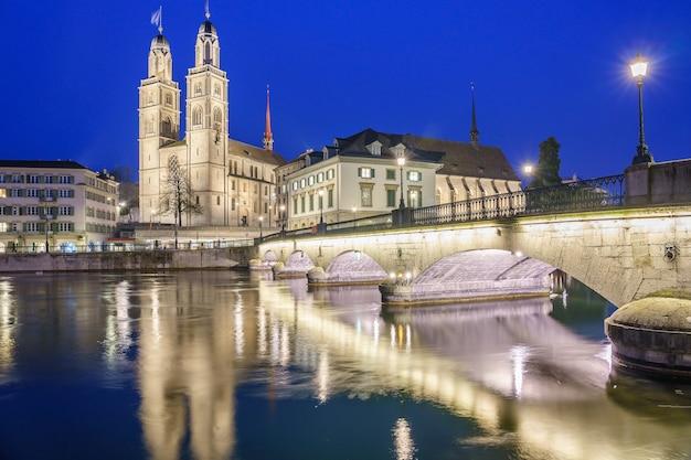 Ciudad histórica de zurich con la famosa iglesia de grossmunster y munsterbucke en el momento del crepúsculo