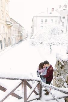 Ciudad de invierno amor. feliz pareja joven en suéteres calientes abrazando cerca del edificio en la ciudad de invierno. mañana de invierno y festivos.
