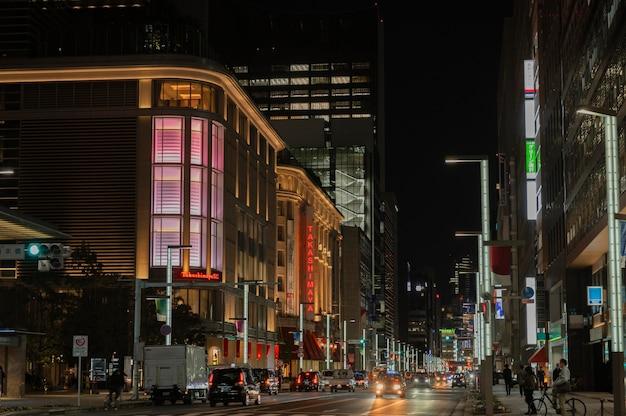 Ciudad de japón por la noche con coches y gente.