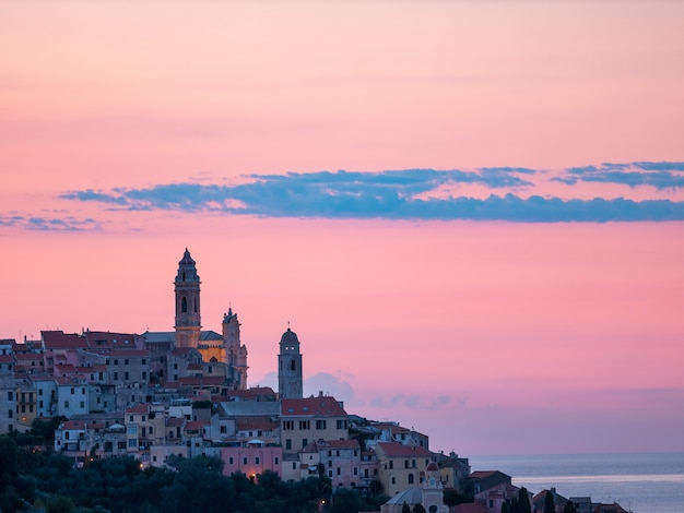 Ciudad medieval de cervo de la visión aérea en la costa mediterránea, riviera de liguria, italia, con la iglesia barroca hermosa y las campanas de torre. turismo de verano en italia.