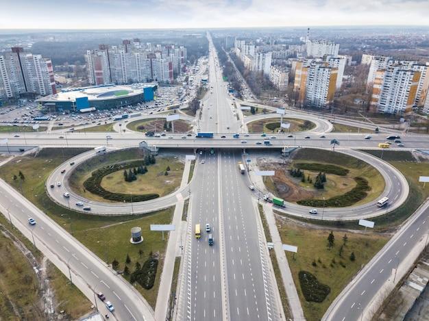 Ciudad moderna con la carretera en forma de quatrefoil en el cruce de carreteras de la plaza odessa alrededor de fondo de un día de otoño de cielo nublado. vista aérea desde el dron. kiev, ucrania