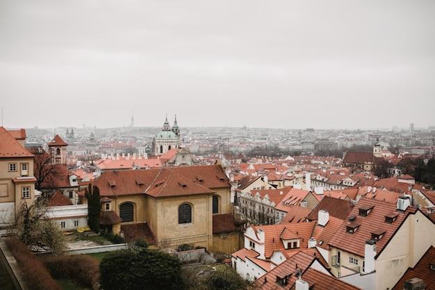 Ciudad de praga con tejados rojos e iglesia en la niebla. vista a la ciudad de la ciudad vieja de praga. tonos de colores grises rústicos