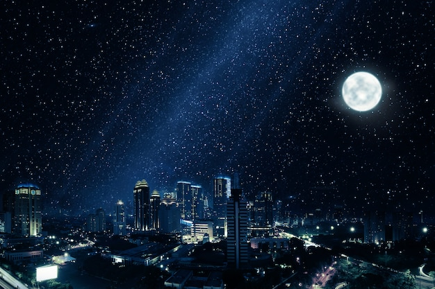 Ciudad resplandeciente con luna brillante y muchas estrellas en el cielo