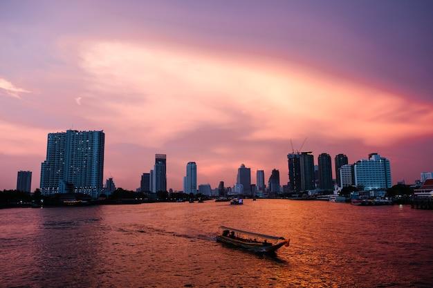Ciudad de río al atardecer y ferry en fondo de bangkok