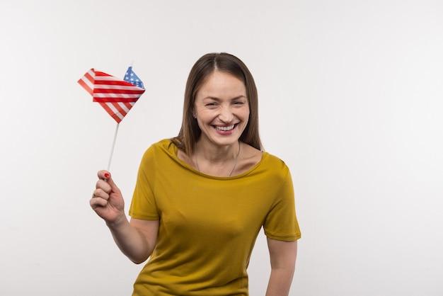 Ciudadano americano. bonita mujer alegre agujereando la bandera de estados unidos mientras expresa sus sentimientos patrióticos