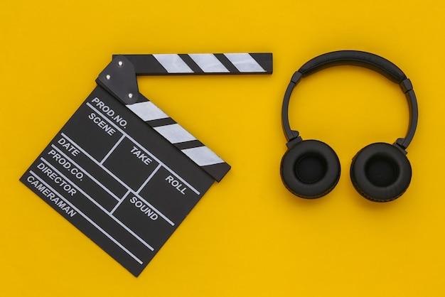 Claqueta de cine y auriculares estéreo sobre un fondo amarillo. vista superior