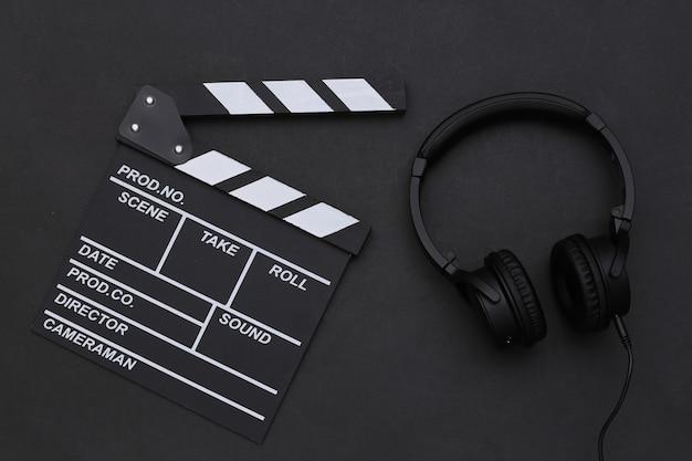 Claqueta de cine y auriculares estéreo sobre fondo negro. vista superior
