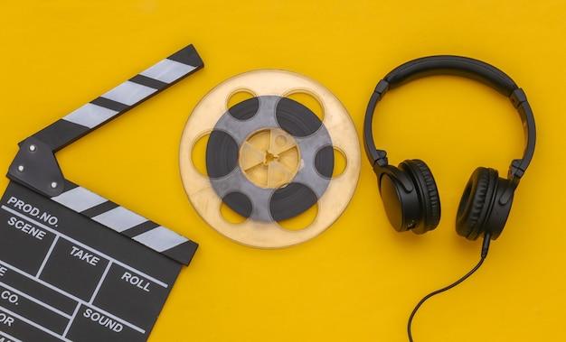 Claqueta de cine, carrete de película y auriculares estéreo sobre un fondo amarillo. vista superior. endecha plana