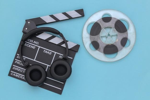 Claqueta de cine, carrete de película y auriculares estéreo sobre fondo azul. vista superior. endecha plana