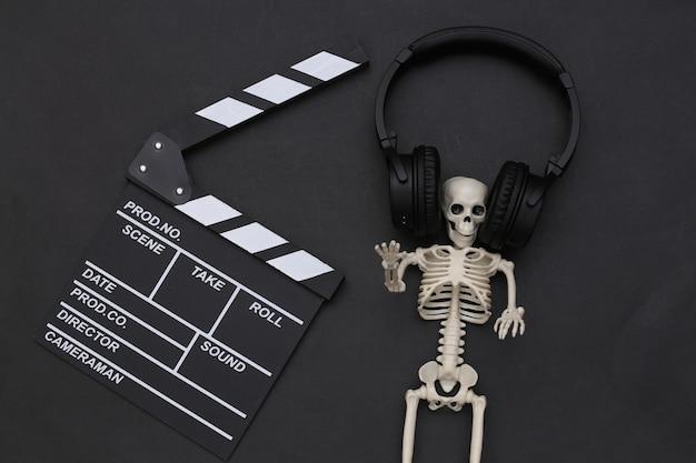 Claqueta de cine y esqueleto en auriculares estéreo sobre fondo negro. película de terror. tema de halloween. vista superior