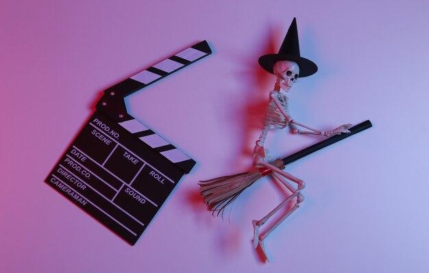 Claqueta de cine con esqueleto de bruja en escoba en luz roja-azul neón degradada. película de terror de halloween