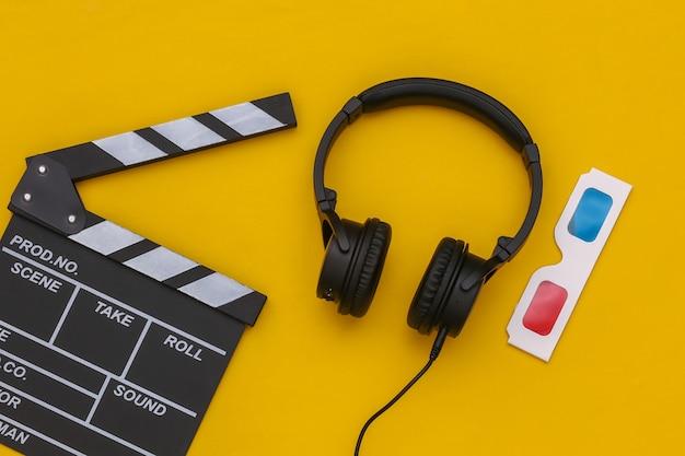 Claqueta de cine, gafas 3d y auriculares estéreo sobre un fondo amarillo. vista superior. endecha plana