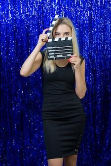 Claqueta en las manos de una hermosa joven rubia con un vestido negro sobre azul brillante