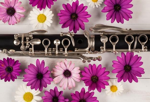 Clarinete con flores en superficie de madera
