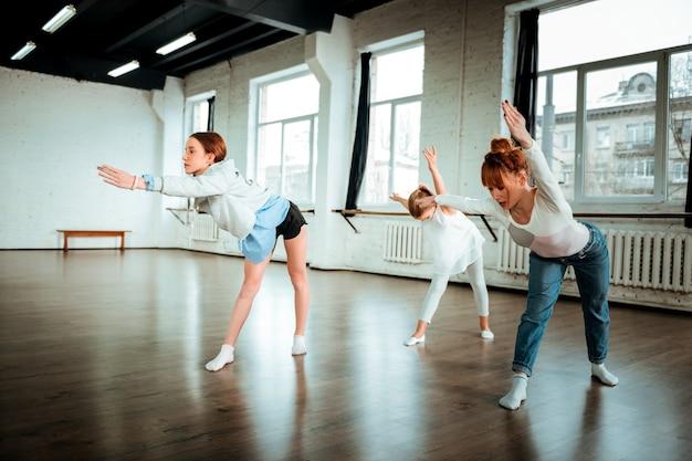 Clase de baile. profesora de danza moderna profesional con cabello rojo mirando enfocado mientras da una lección en el estudio