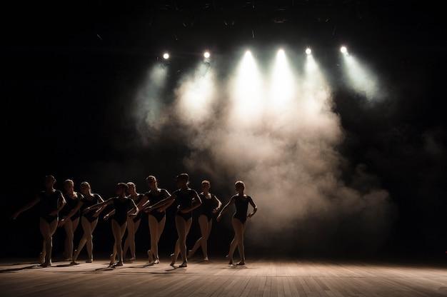 Clase de ballet en el escenario del teatro con luz y humo. los niños se dedican al ejercicio clásico en el escenario.