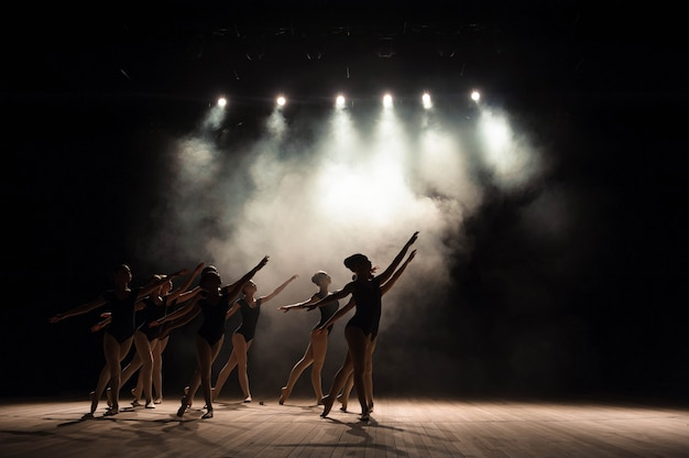Clase de ballet en el escenario del teatro con luz y humo. los niños participan en ejercicio clásico en el escenario.