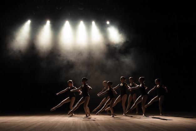 Clase de ballet en el escenario del teatro con luz y humo. los niños participan en ejercicios clásicos en el escenario.
