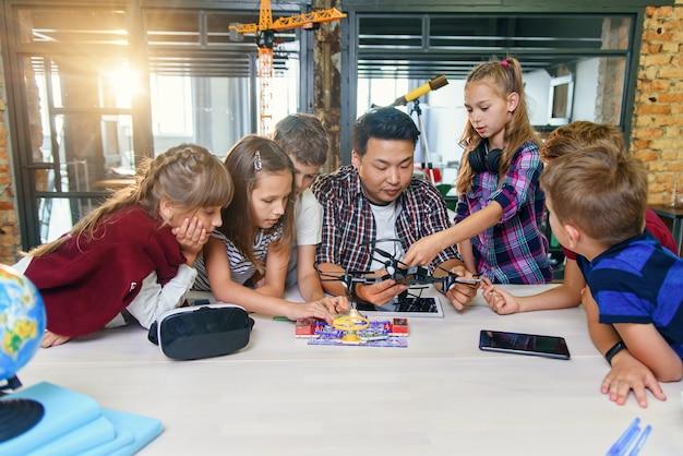 En la clase de física y mecánica, un joven maestro asiático demuestra un quadcopter para alumnos caucásicos en clase en una escuela inteligente moderna. ciencia, dron, ingeniería y concepto de futuro.