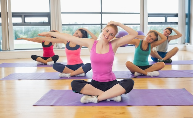 Clase de fitness e instructor estirando las manos sobre colchonetas de yoga