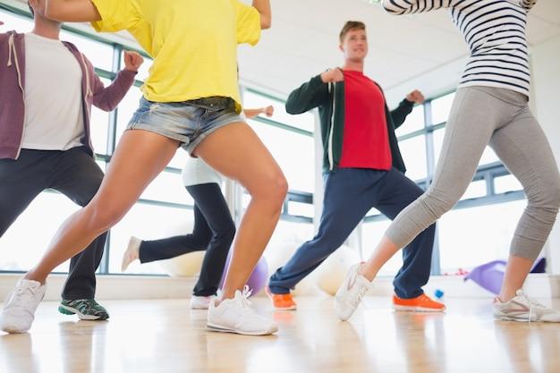 Clase de fitness e instructor haciendo ejercicio de pilates