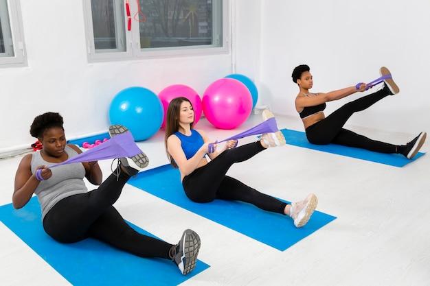 Clase de fitness haciendo ejercicios en colchoneta