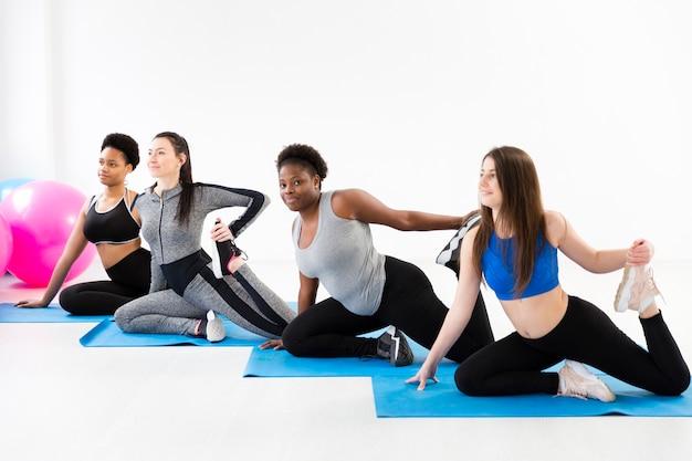 Clase de gimnasia haciendo ejercicio en la estera