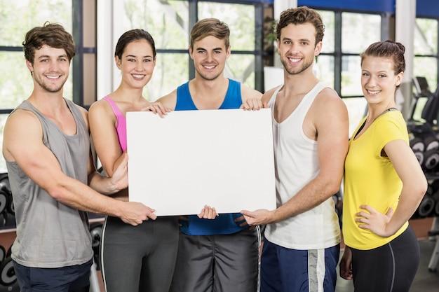 Clase de gimnasia sosteniendo una tarjeta blanca en gimnasio
