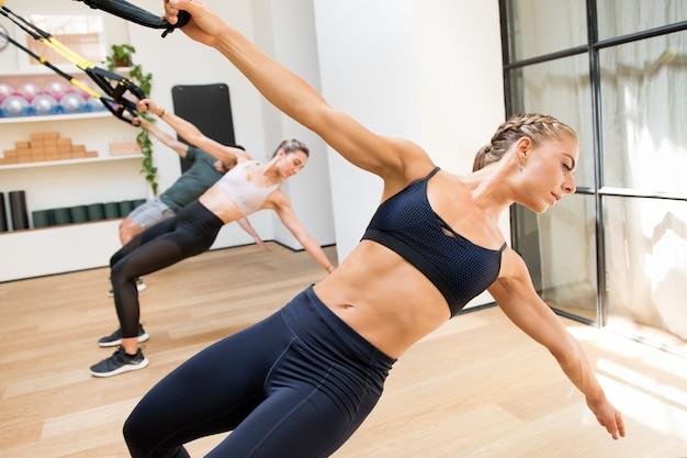 Clase haciendo ejercicios trx power pull en un gimnasio
