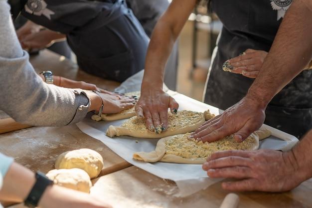 Clase magistral culinaria. primer plano de manos de personas preparando khachapuri. pan de queso georgiano tradicional. comida georgiana.