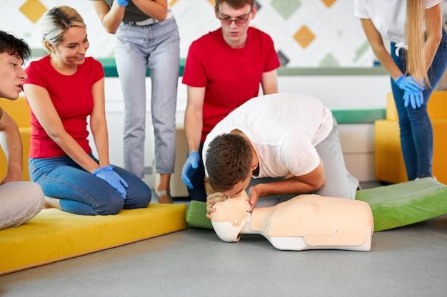 Clase de reanimación cardiopulmonar con instructor joven que demuestra ayuda de primeros auxilios